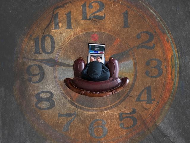 Vue de dessus d'un codeur installé dans un fauteuil cuir au milieu d'une horloge peinte au sol