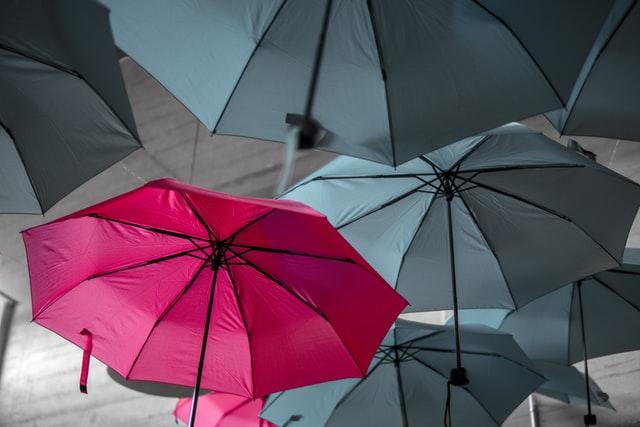 Un parapluie rose ouvert au milieu d'autres parapluies gris