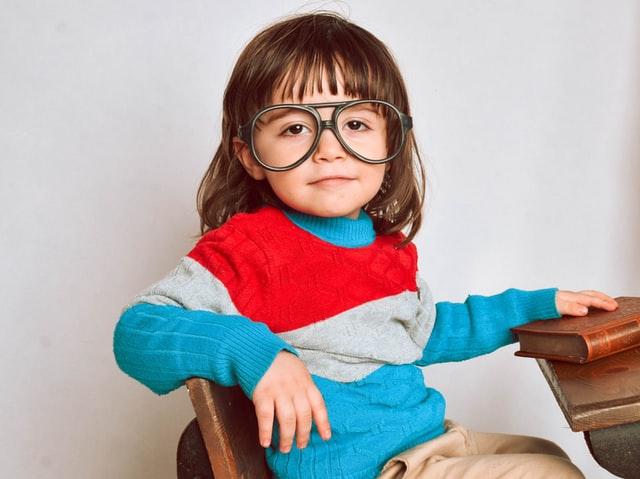 petite fille avec un pull à rayures et de grandes lunettes assise à une table d'école